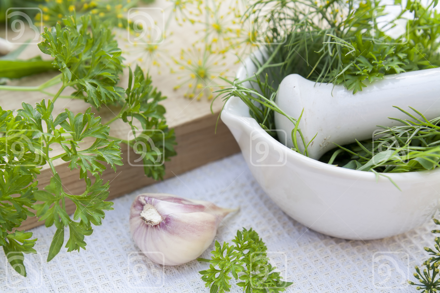 Herbs in the pestle and garlic on the table