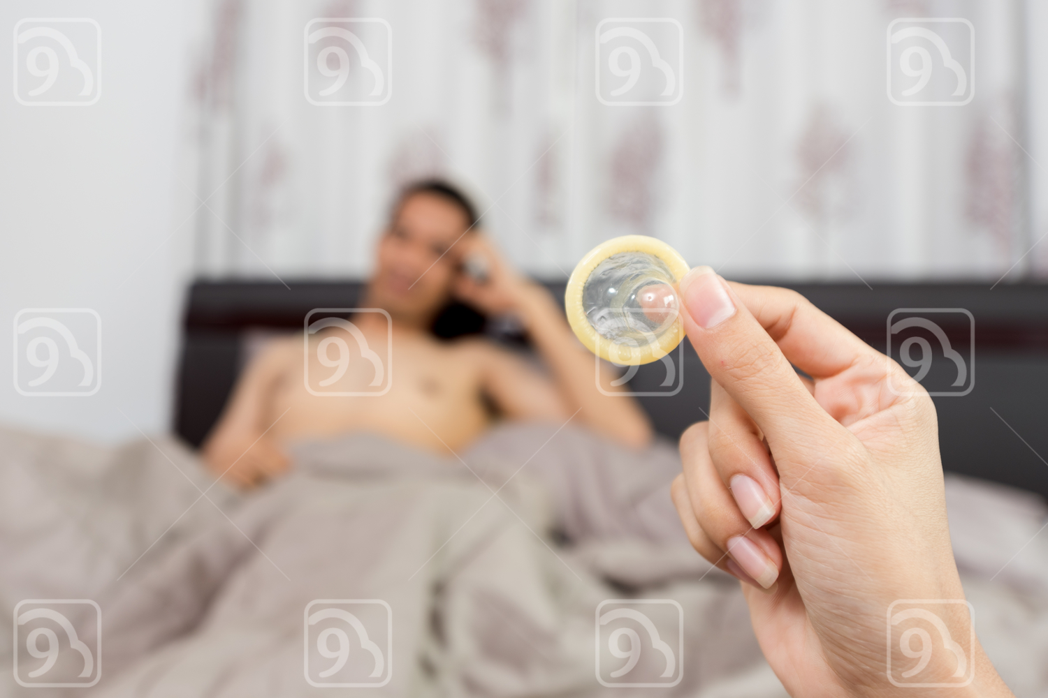 Woman showing a condom on bed