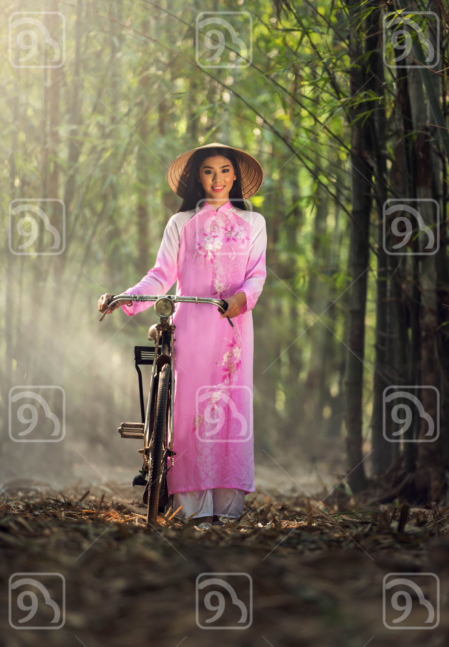 Portrait of Vietnamese girl in traditional dress with bicycle