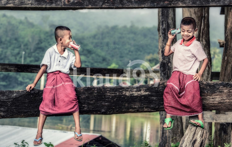 Thai boys talking on a can phone