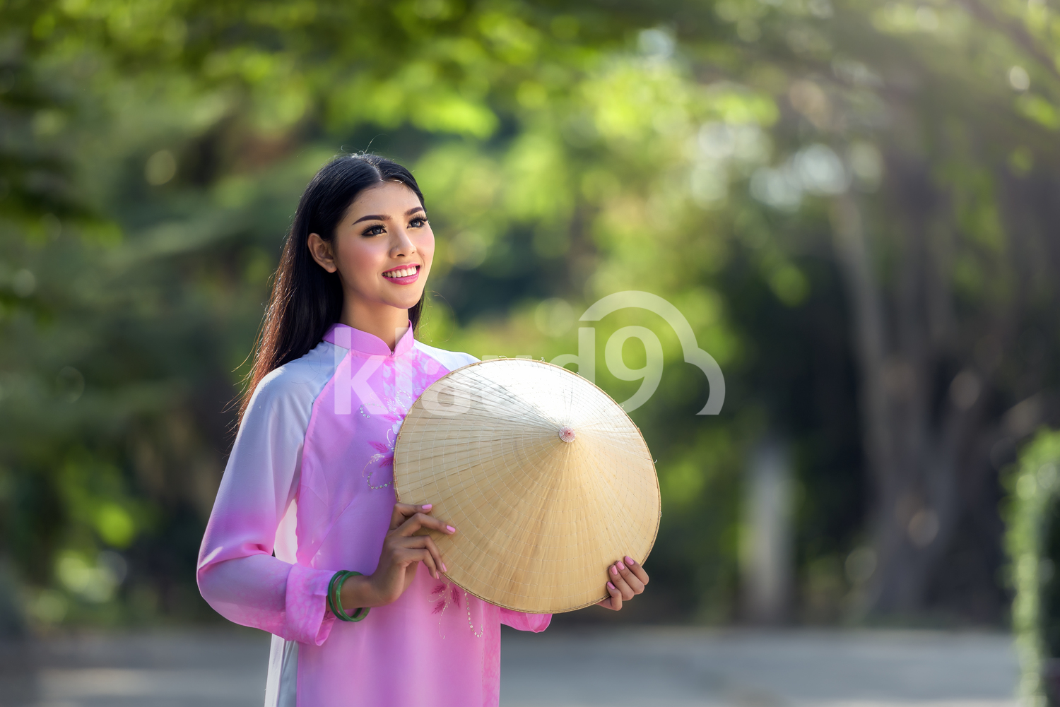 Portrait of Vietnamese girl in traditional dress holding a straw hat