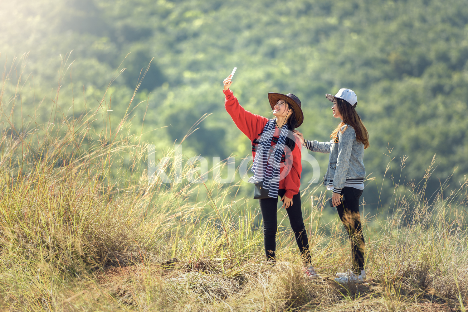 Woman taking selfies with smartphone at mountain peak