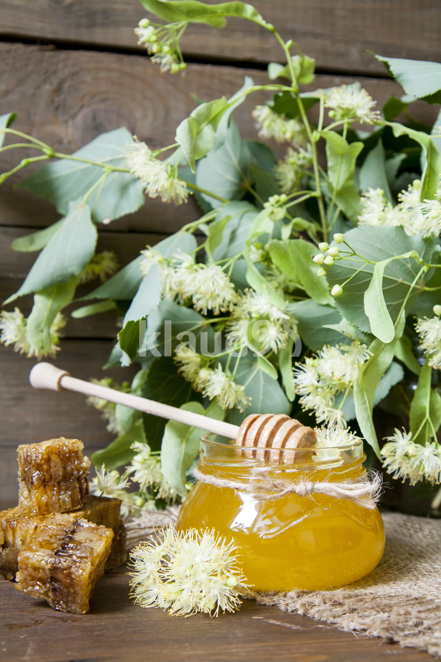 Jar with honey, honeycomb with pollen and linden flowers