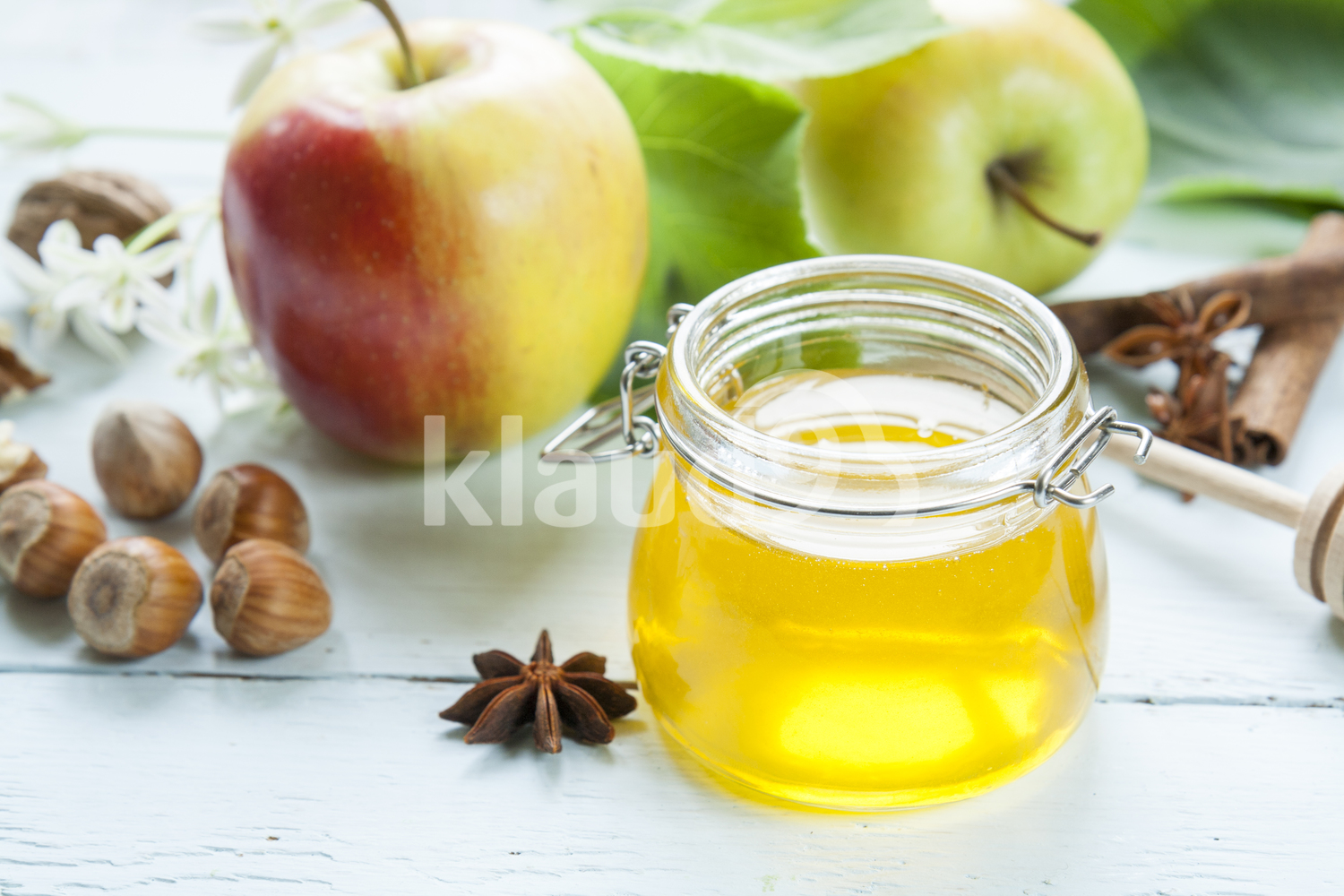 Apple and honey on light wooden table