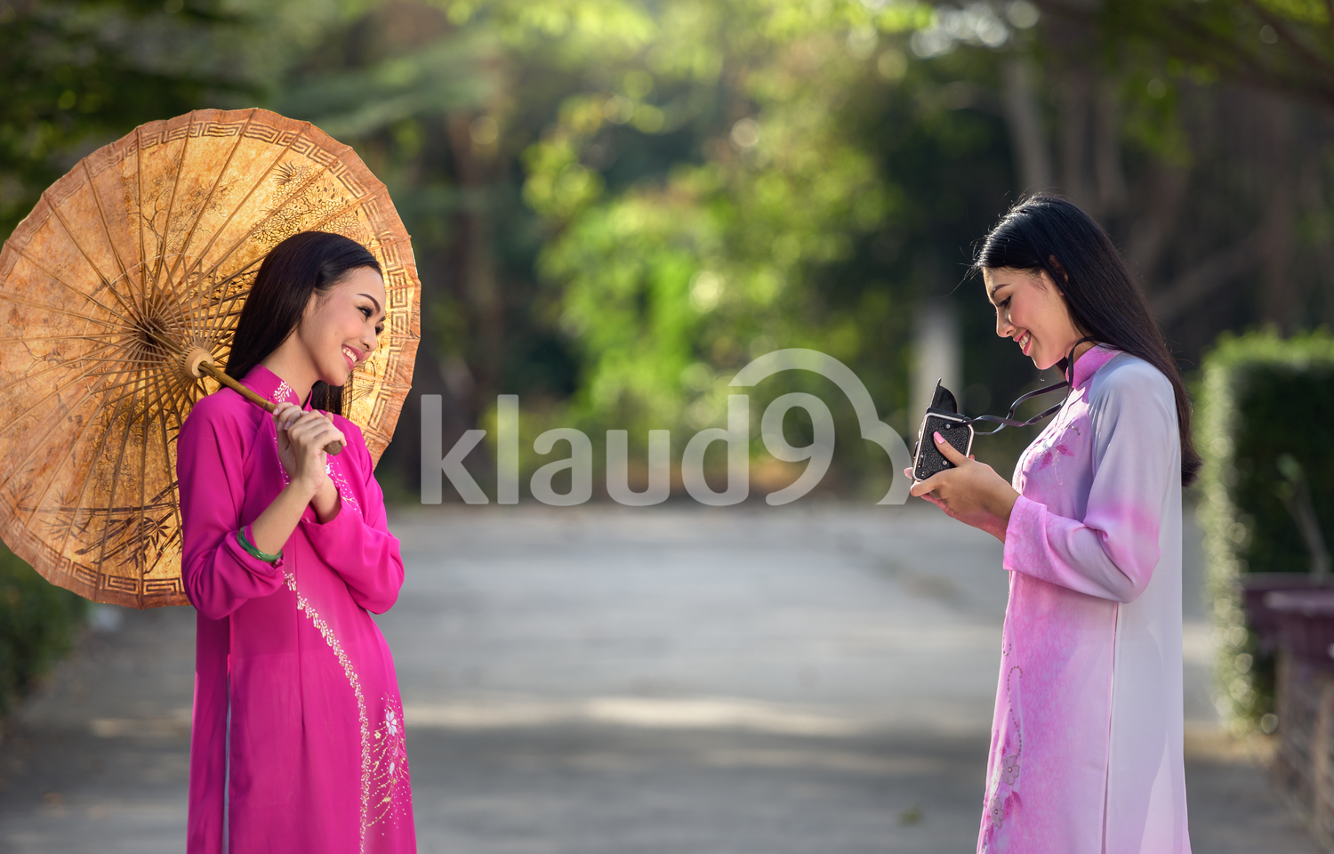 Portrait of Vietnamese girls in traditional dress with camera