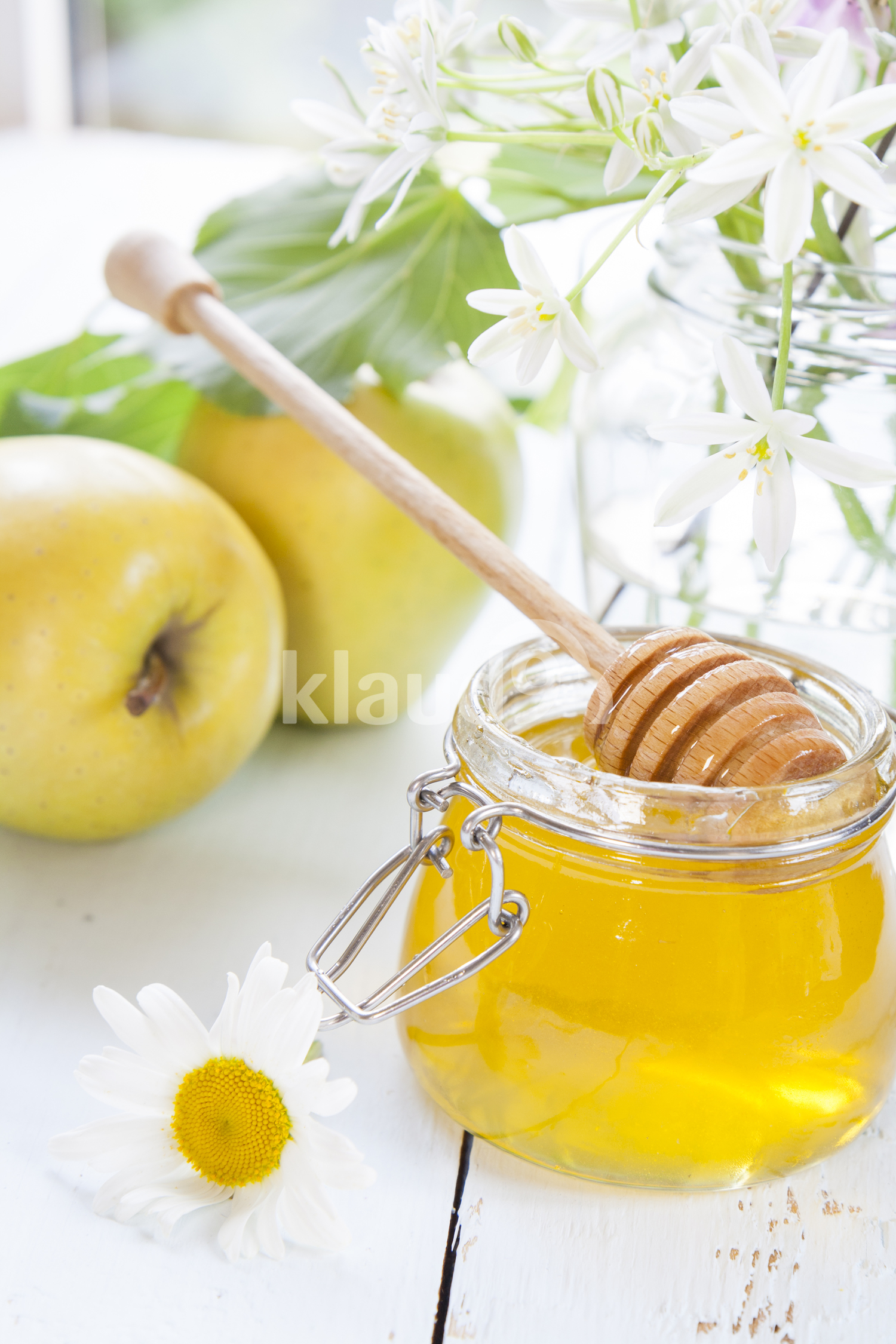Apple, honey and flowers on light wooden table