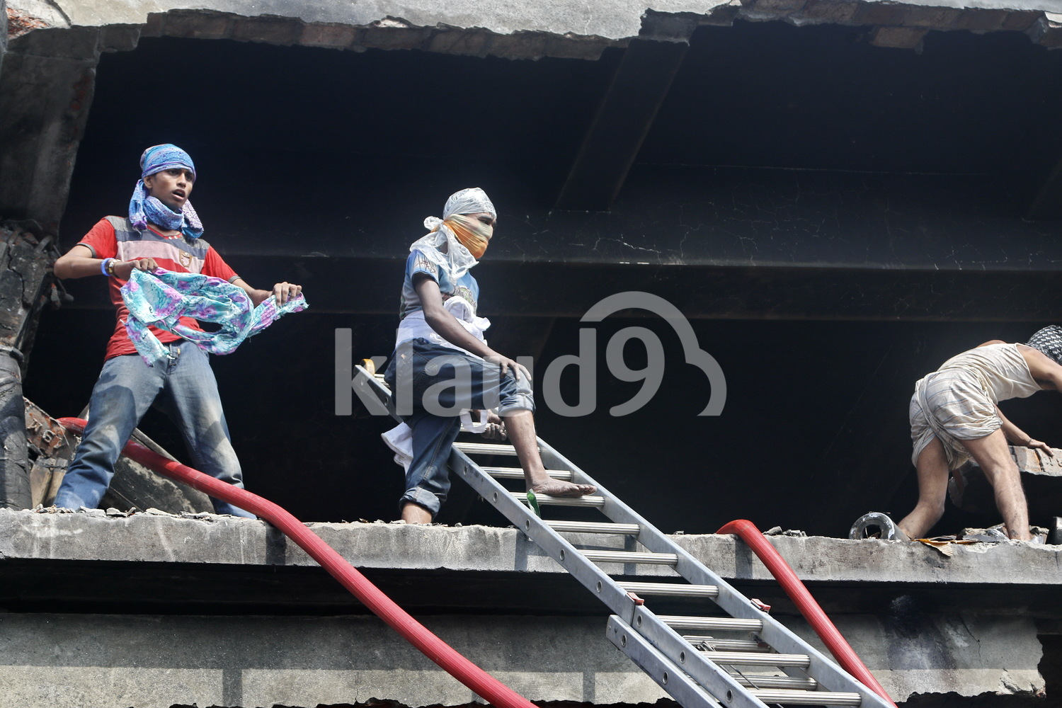 Bangladeshi rescuers at aftermath of factory fire