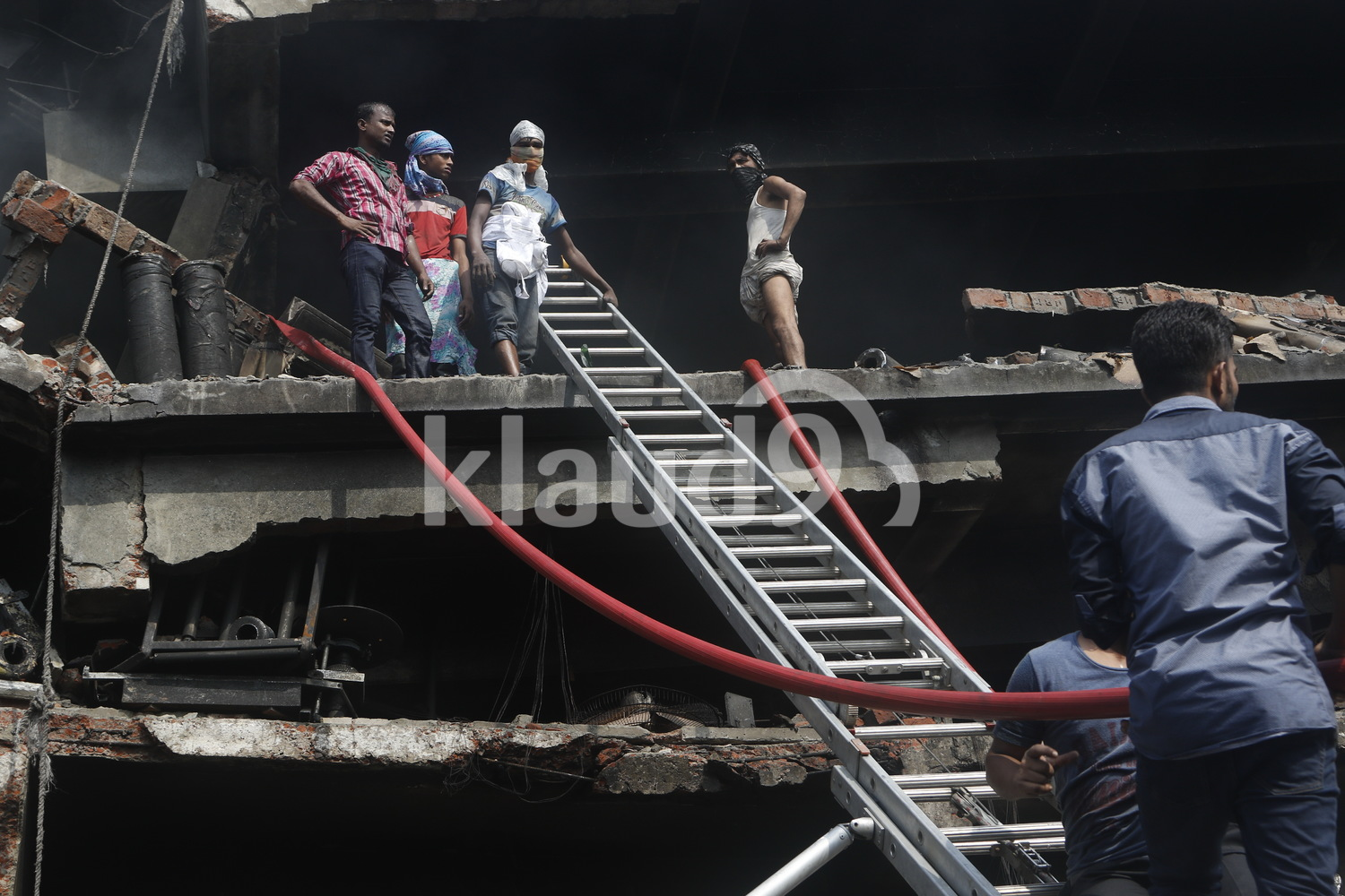 Rescuers surveying the aftermath of a factory fire.