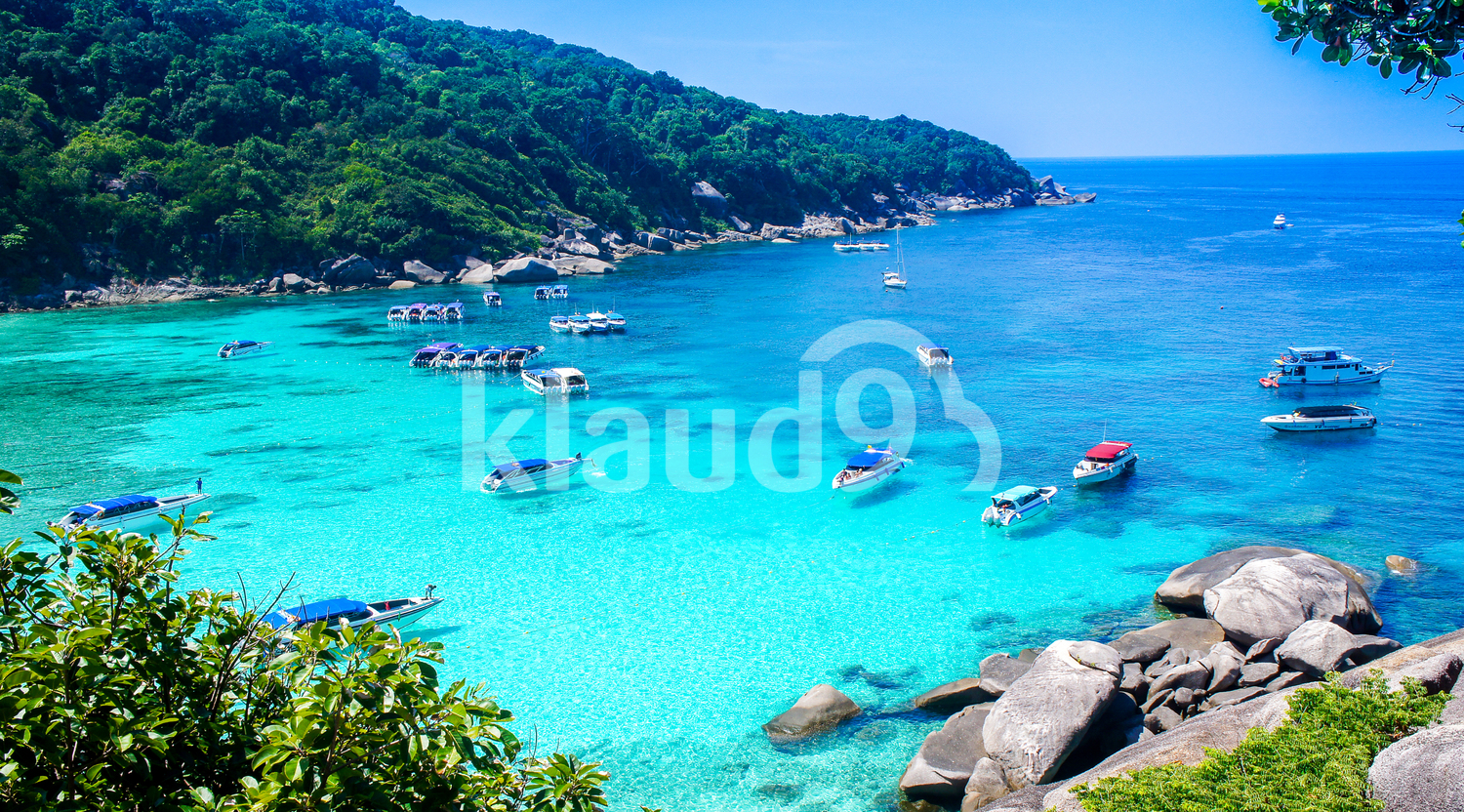 An aerial view from a rocks' mountain looking on a shallow sea which there are many yachts stopping by for the tourist to enjoy the sea water and the beach.