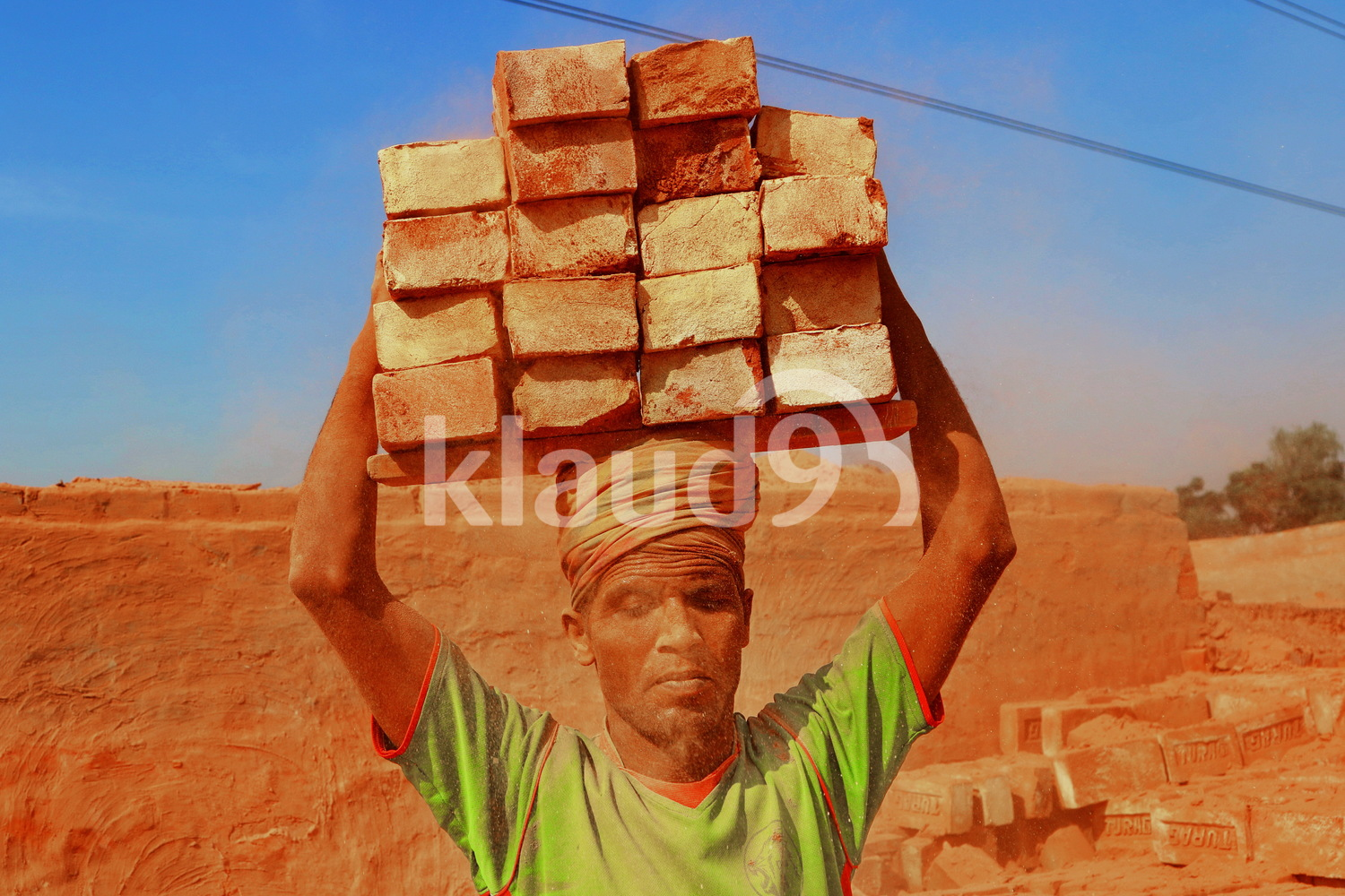 Indian labourer carrying bricks