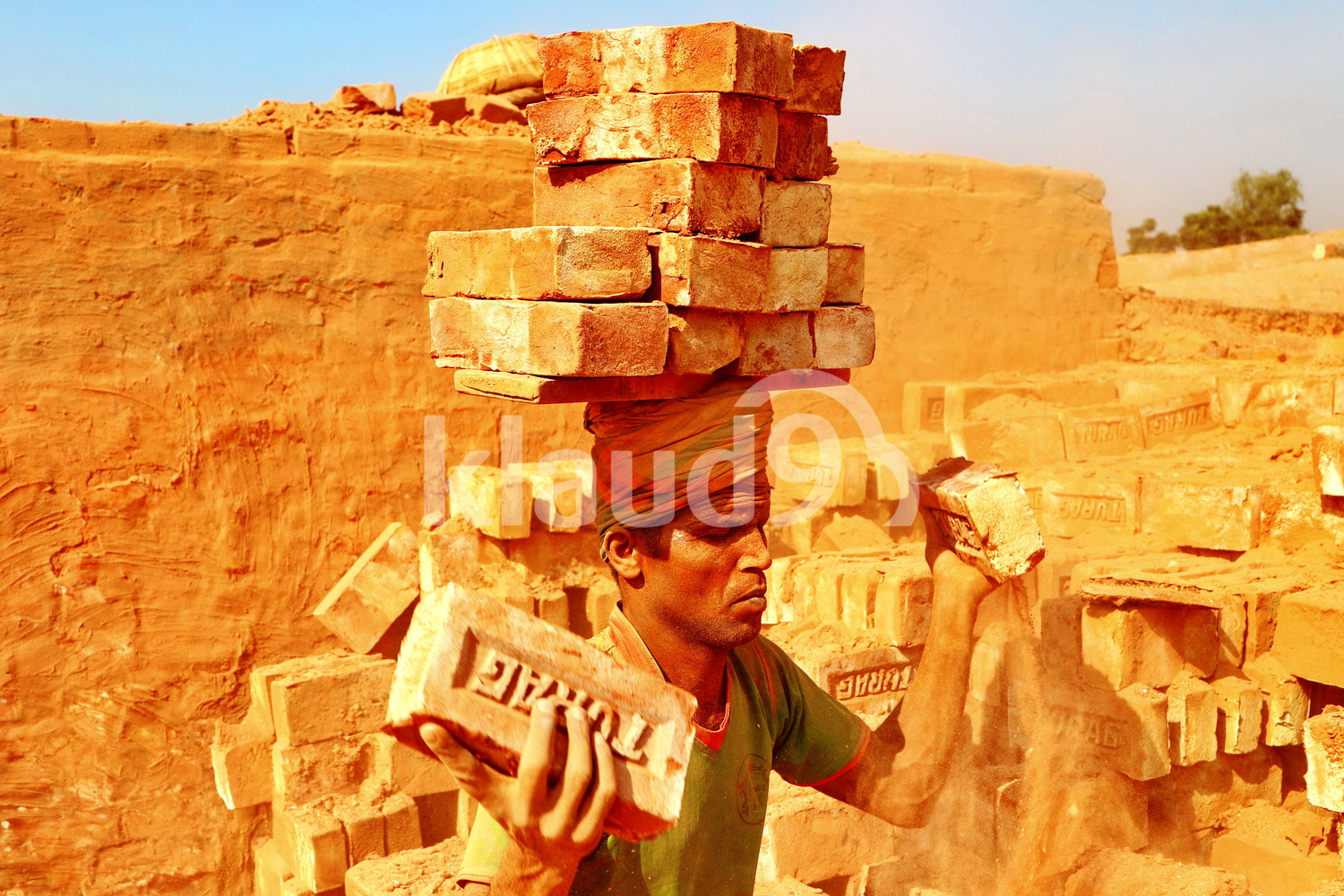 Indian man carrying bricks on his head