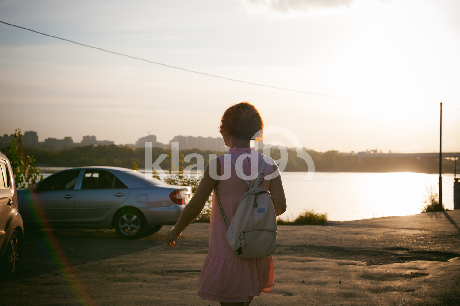 girl in a pale pink dress with red hair and a backpack goes to his car in the parking lot by the river, sunset on a summer day