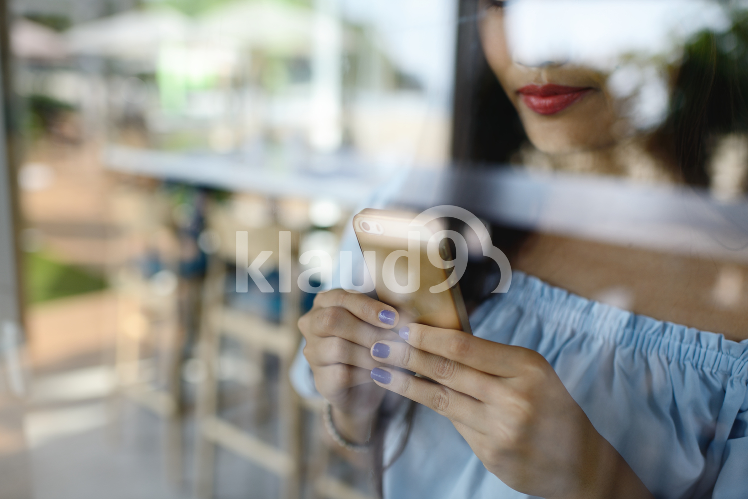 Woman texting on her phone through glass