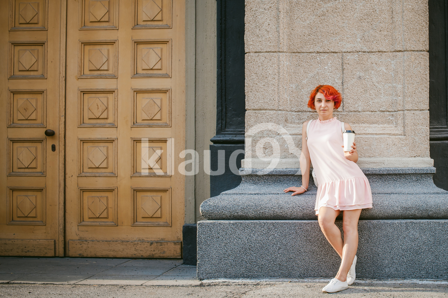 Portrait of a red haired lady drinking coffee