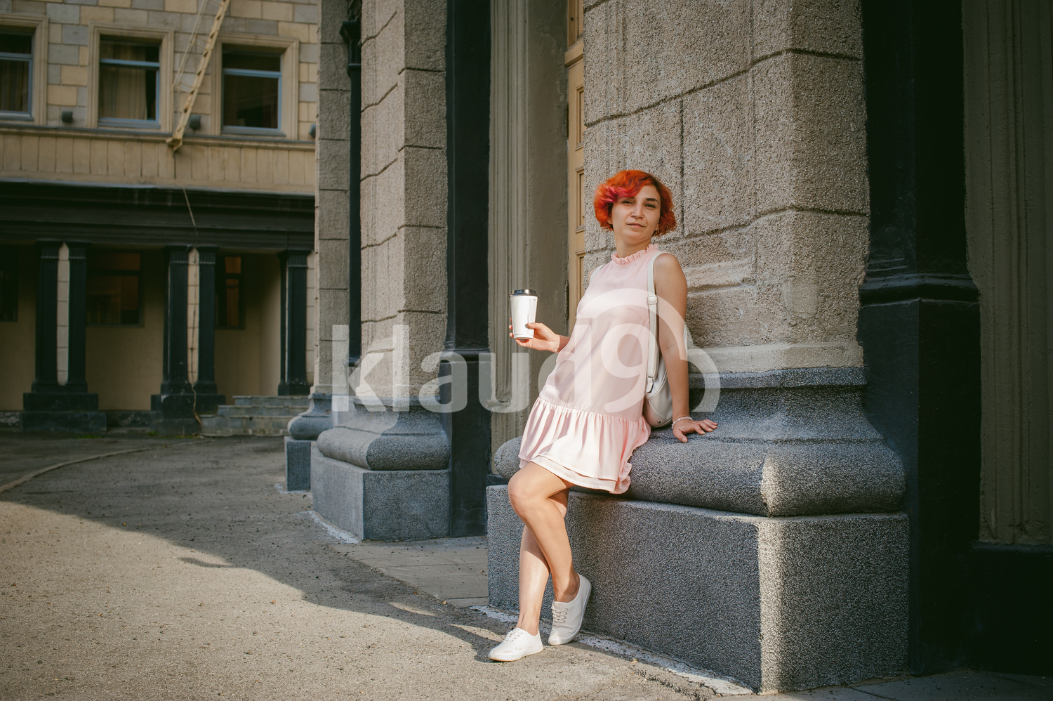 Portrait of a red haired lady sipping on coffee