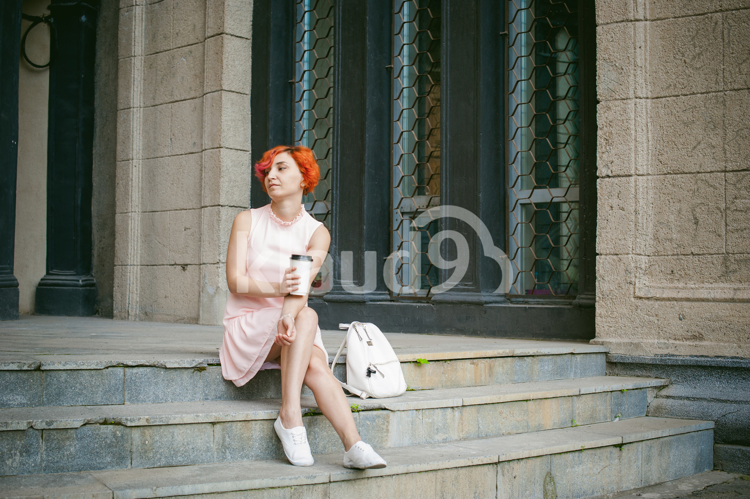 Red haired lady looking lost in her thoughts with a coffee cup