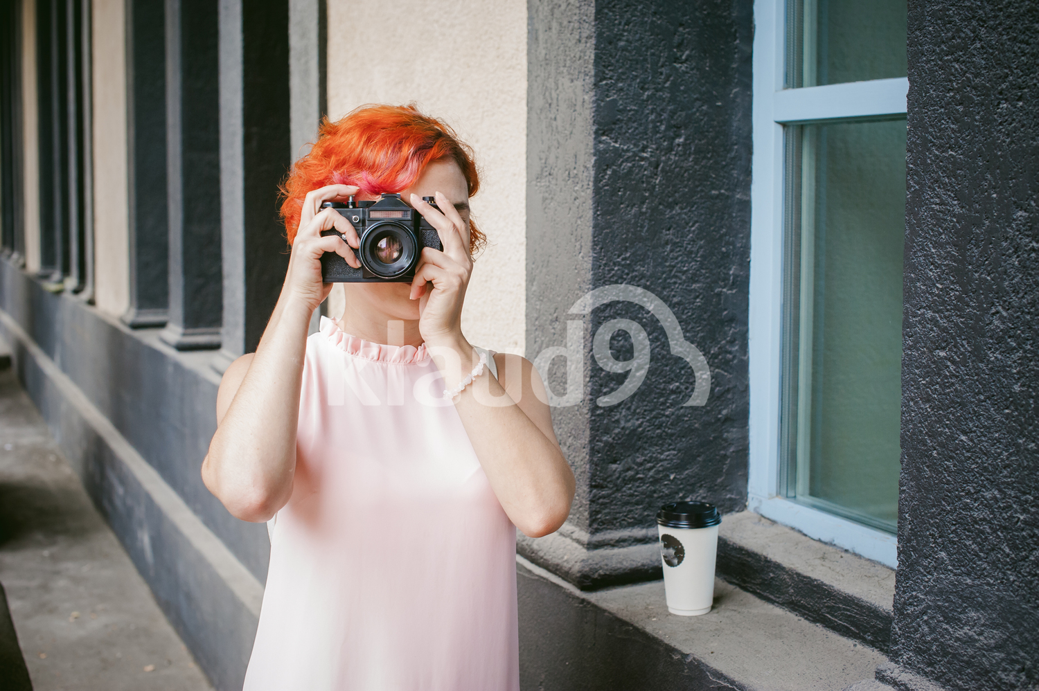 Red head with a film camera