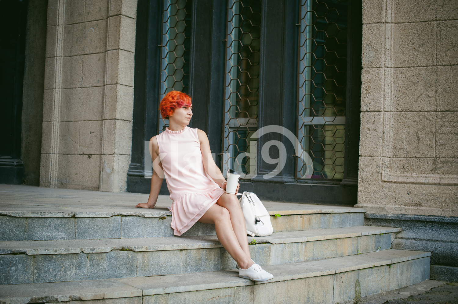 drinks coffee from a cup. woman with dyed red hair in a pale pink dress drinking coffee, holding a paper cup of coffee to go, sitting on the steps outside a summer day.