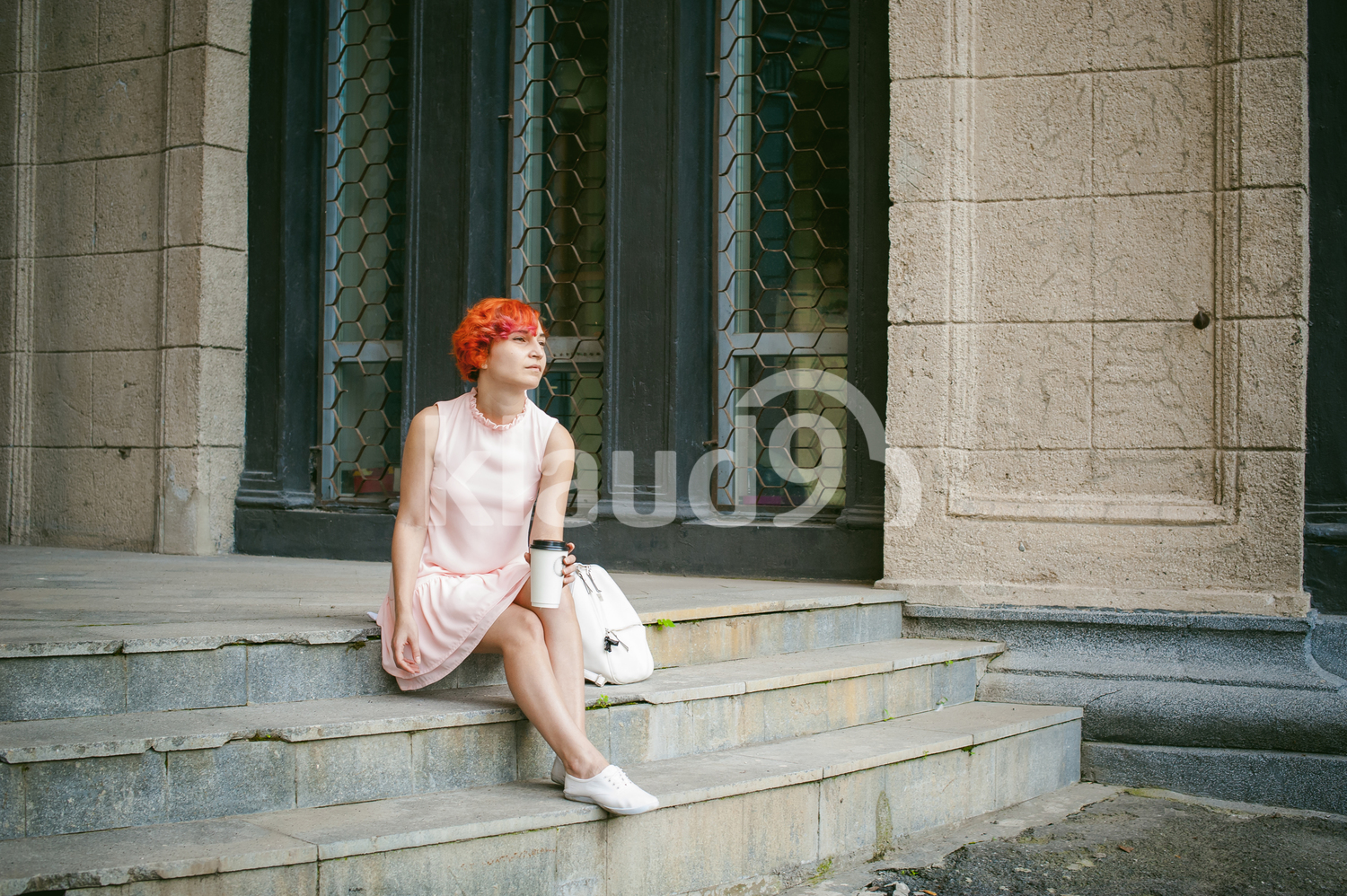 Lady with red hair holding a coffee cup