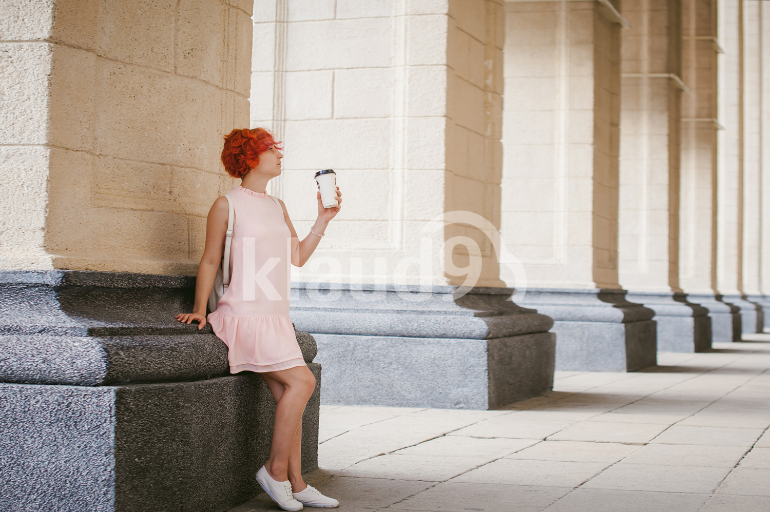 Woman in pale pink dress and a coffee cup