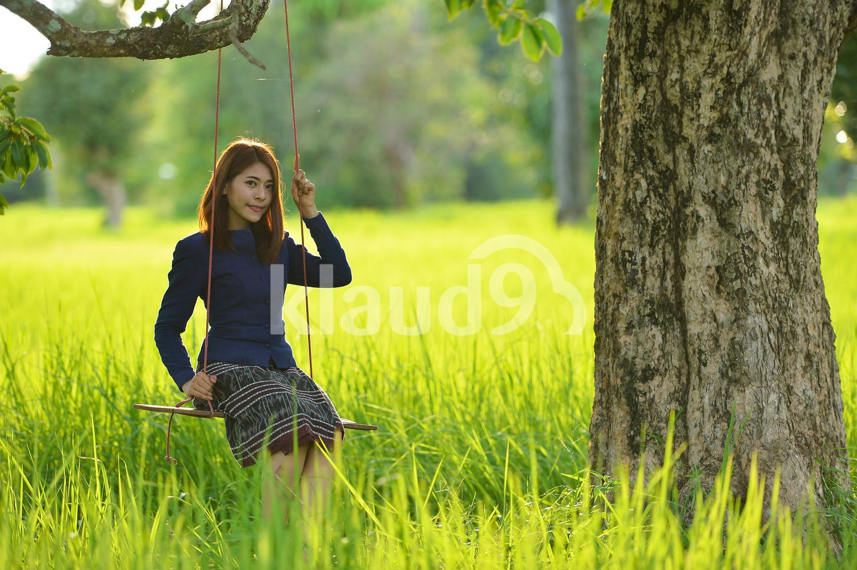 Thai woman in the fields on a swing