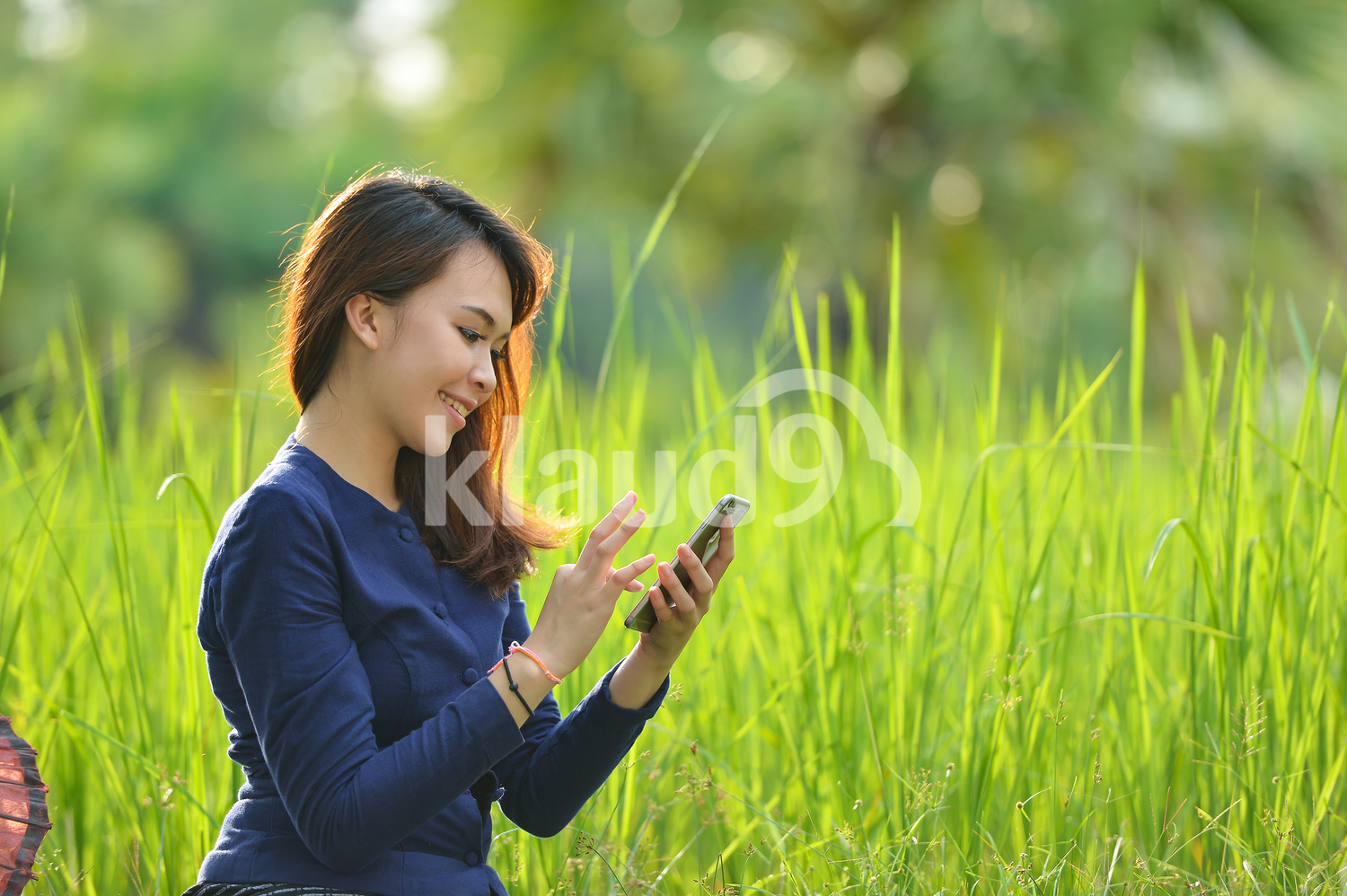 Beautiful Thai lady with smart phone in the fields