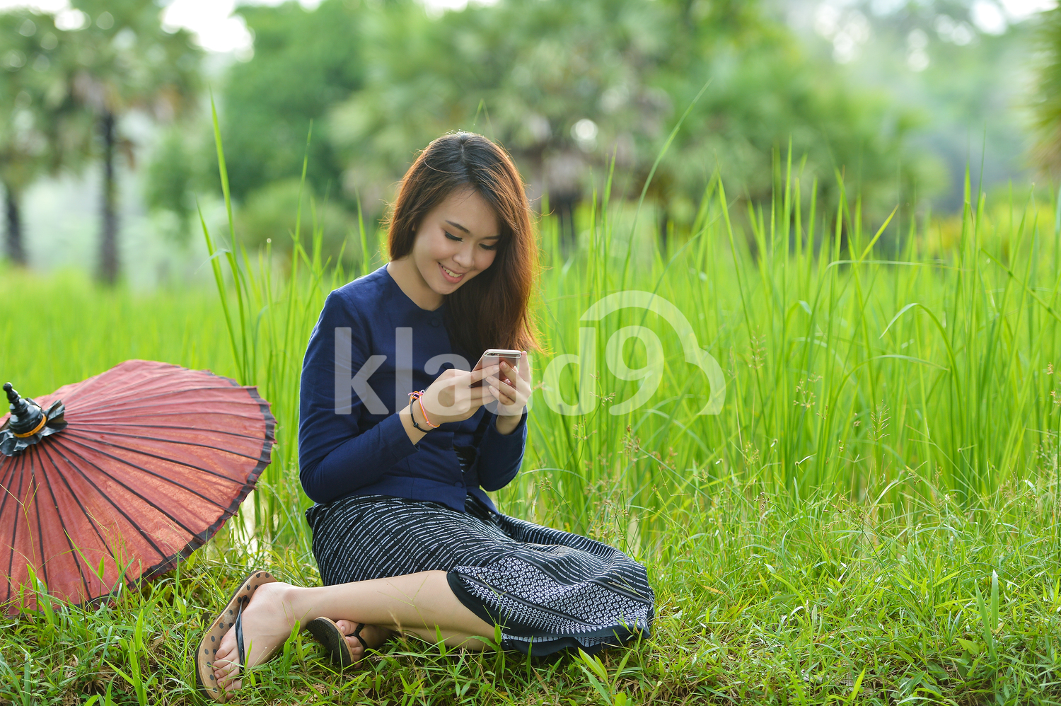 Beautiful Thai woman using her cellphone in the fields
