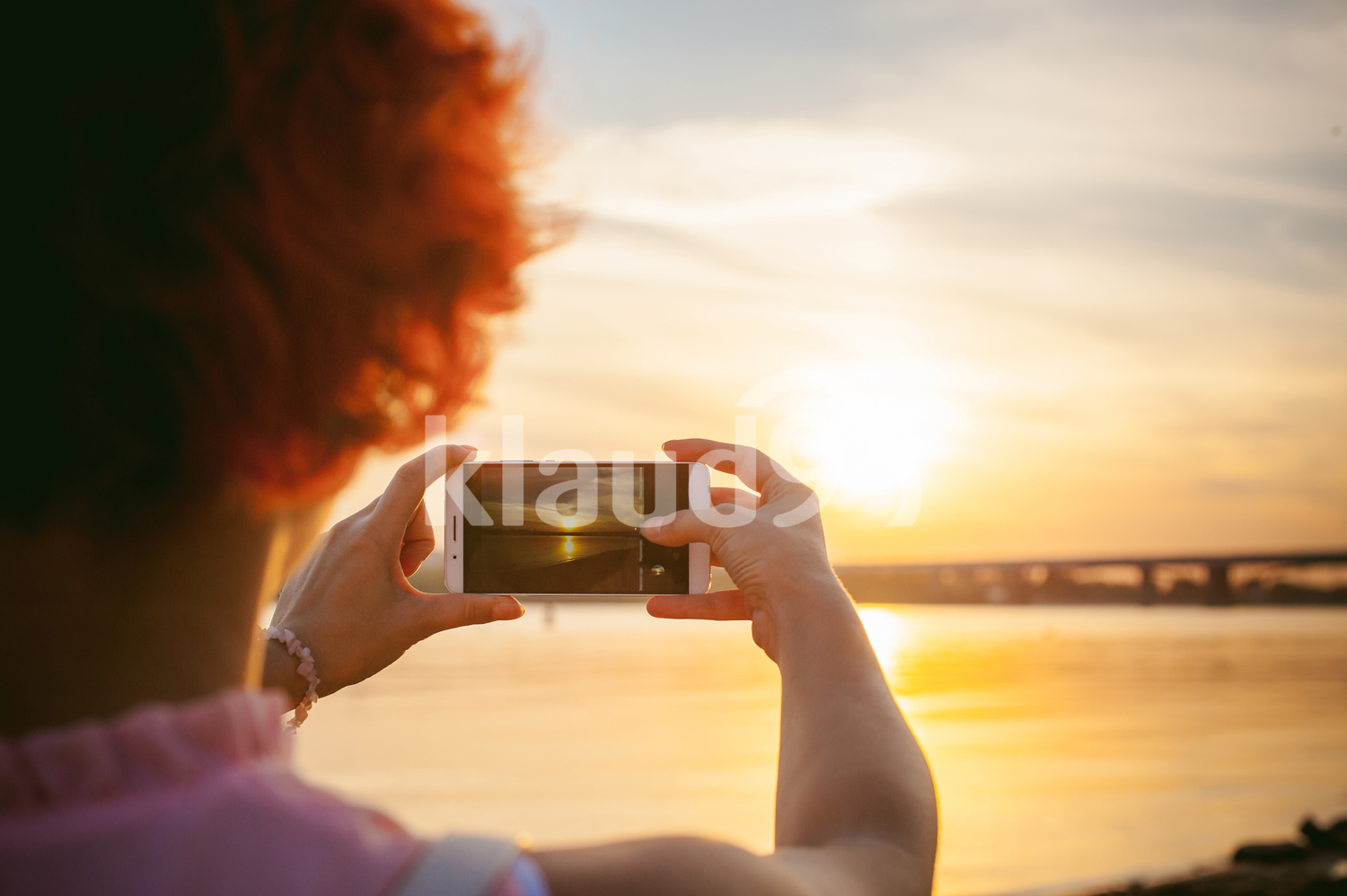 Lady shooting a landscape on a cellphone