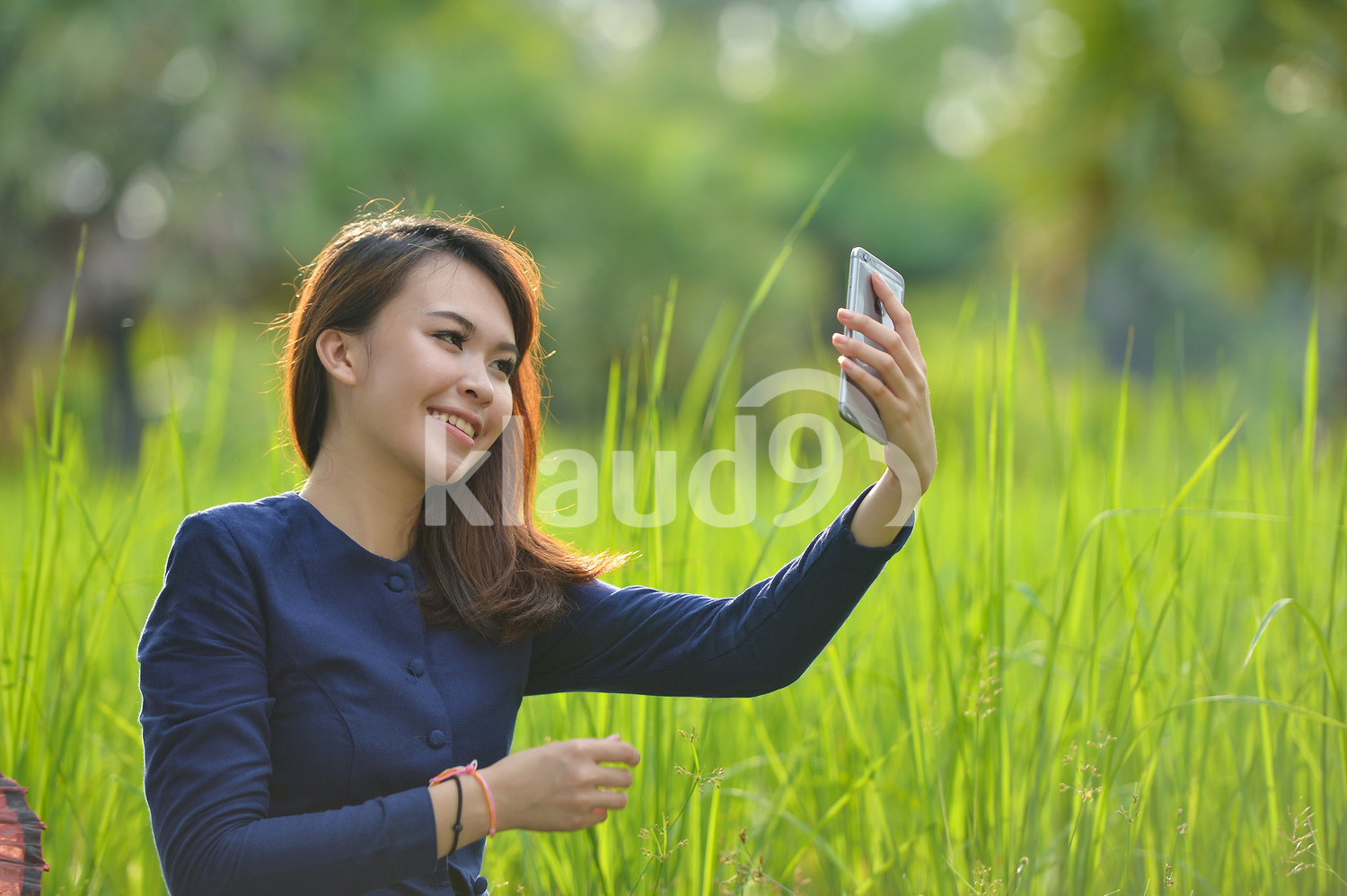 Thai lady using a handphone in the paddy fields