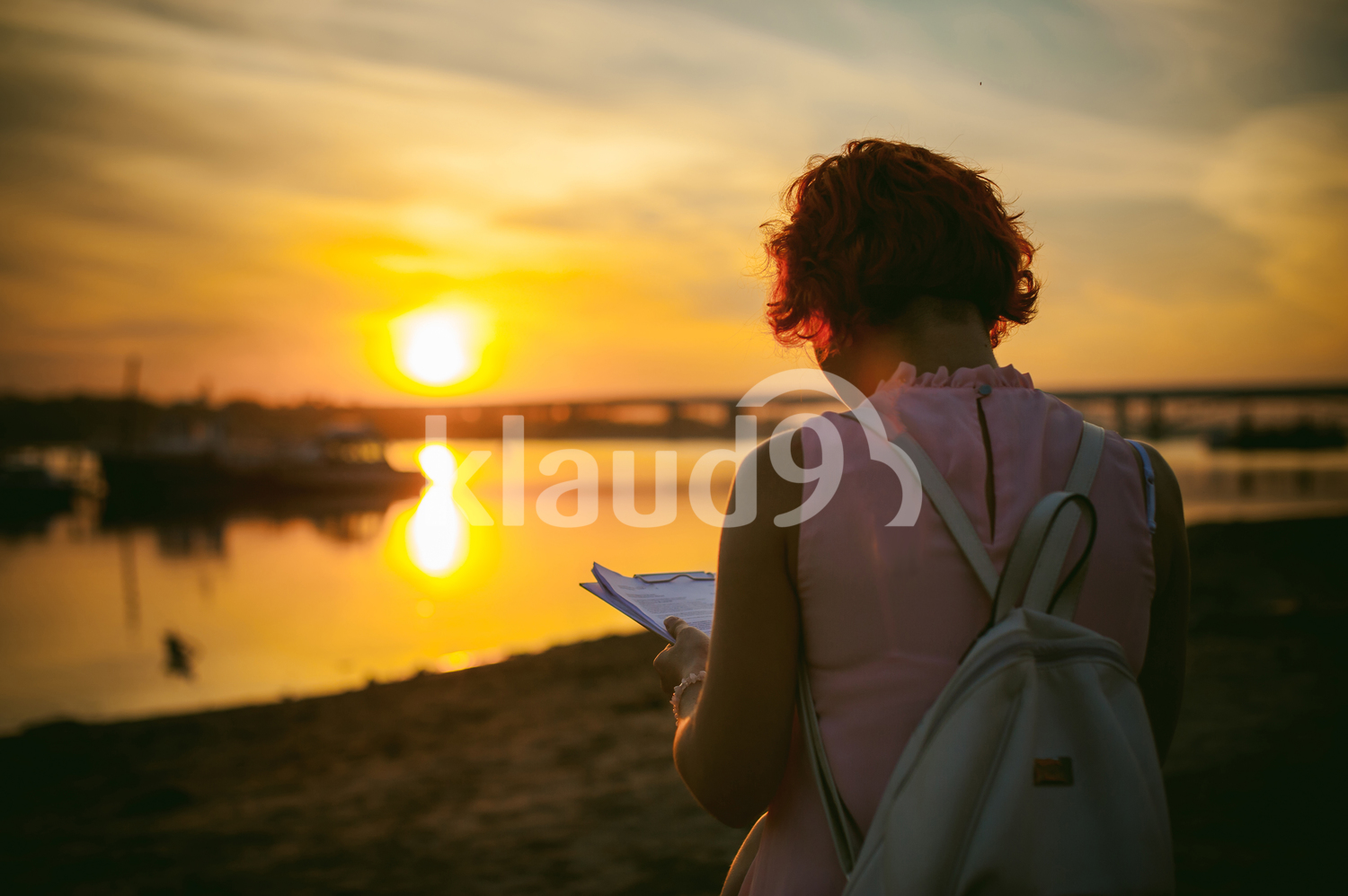 Woman with dyed red hair in a pale pink dress against a beautiful sunset