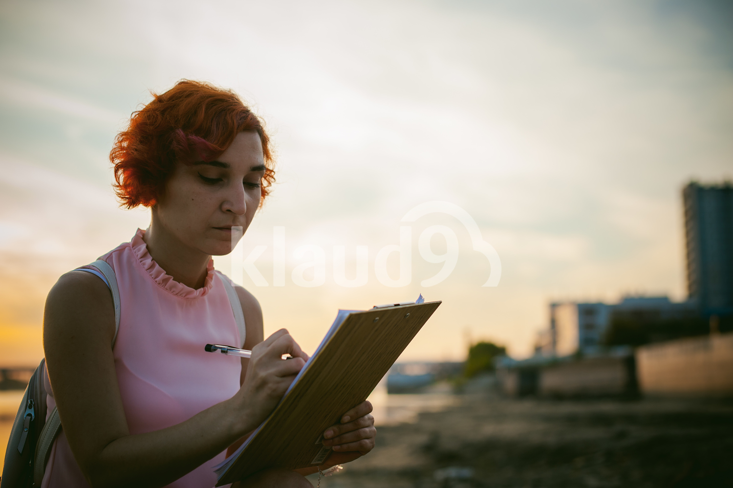 Woman with dyed red hair signing documents