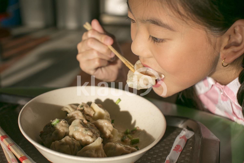 Girl eating dumplings in a hawker