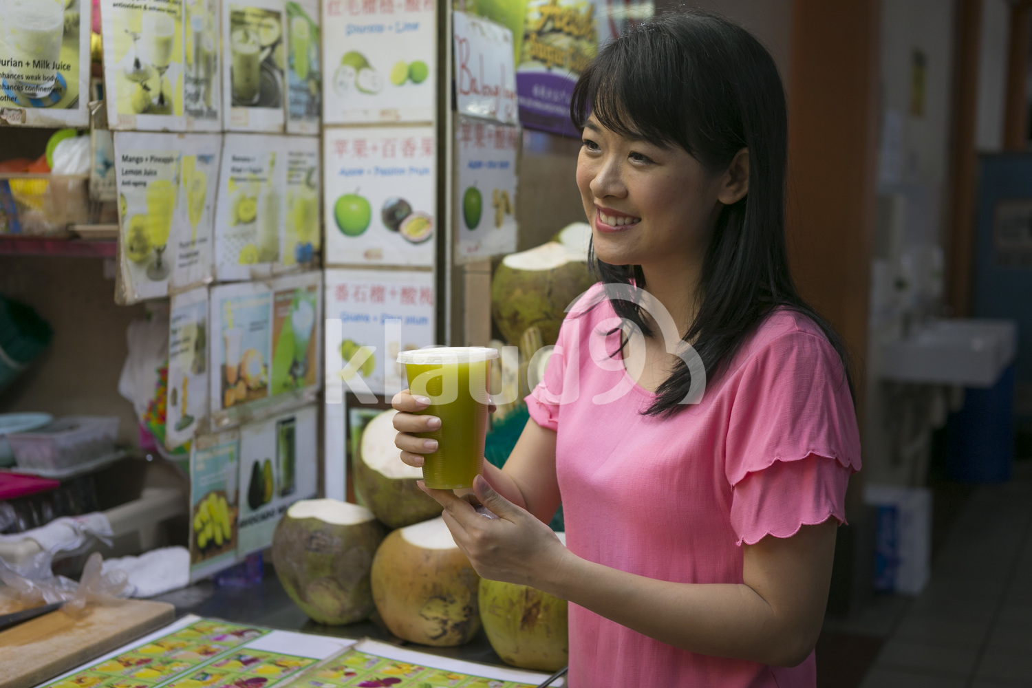Woman holding a fresh fruit juice at hawker centre