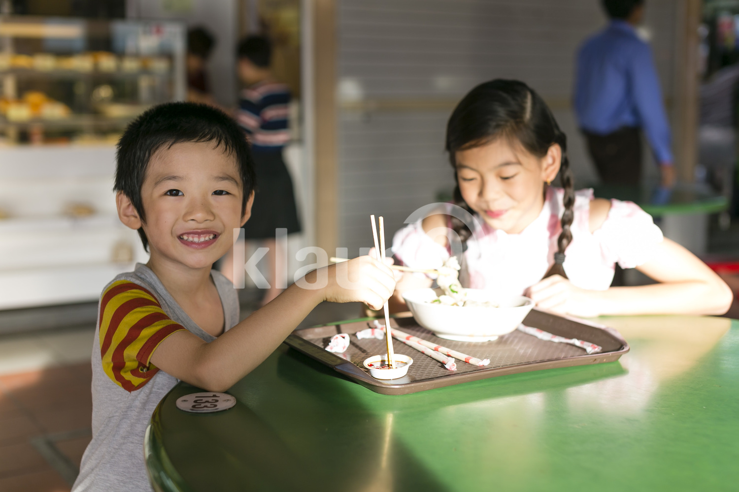 Brother and sister eating in a hawker