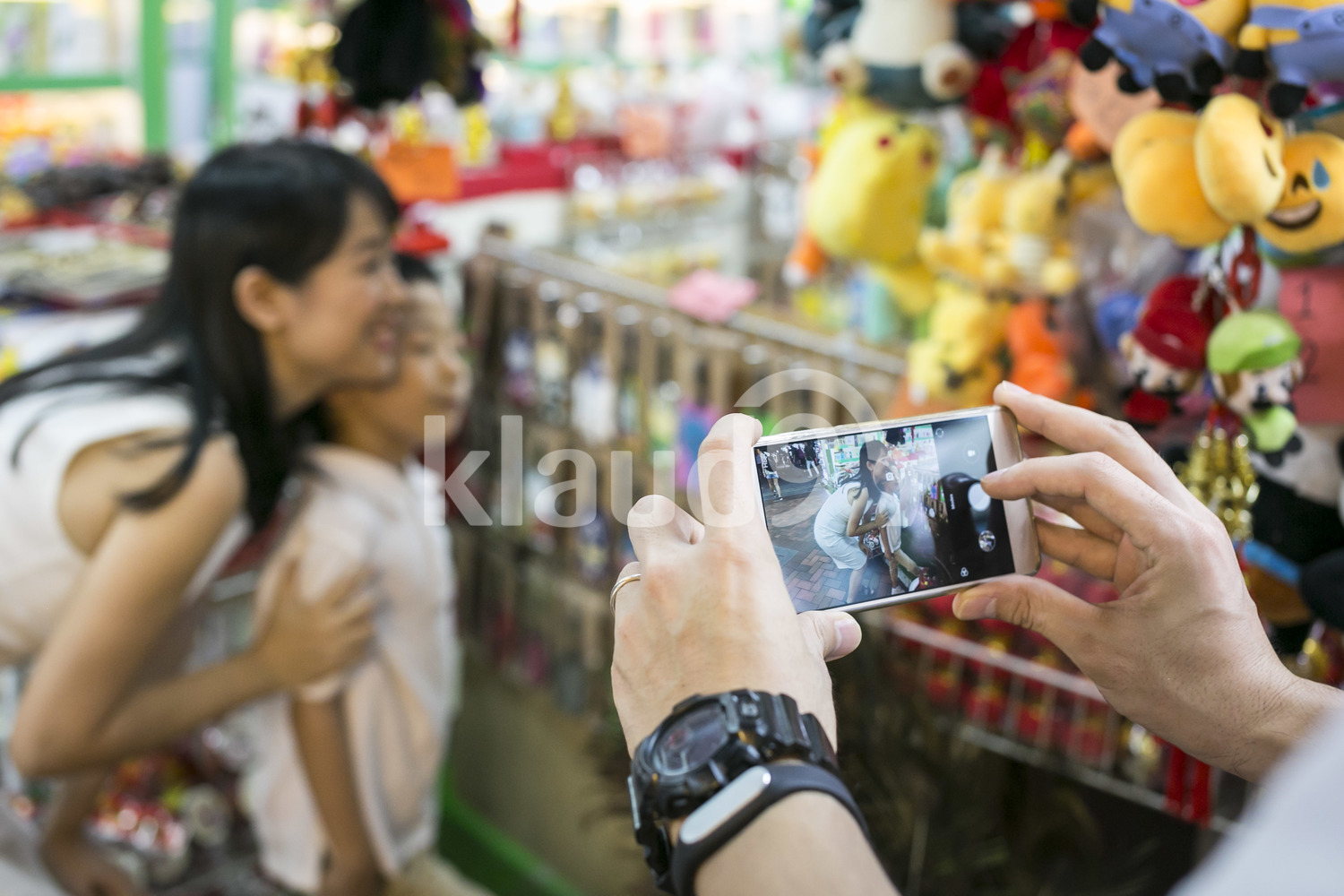 Father takes a photo with his phone in Chinatown