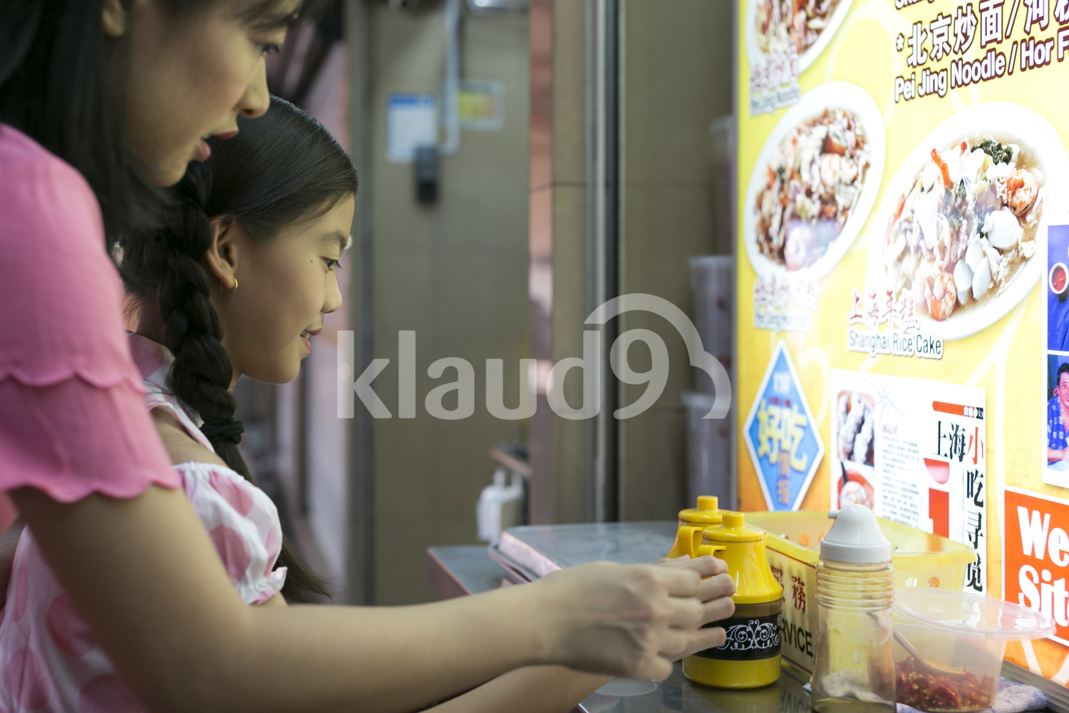 Mother and daughter in a hawker centre ordering food