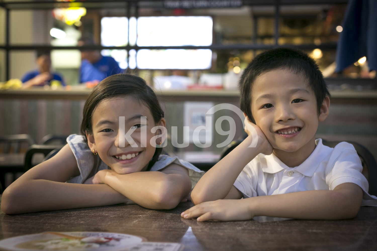 Brother and sister waiting for dinner in Chinatown