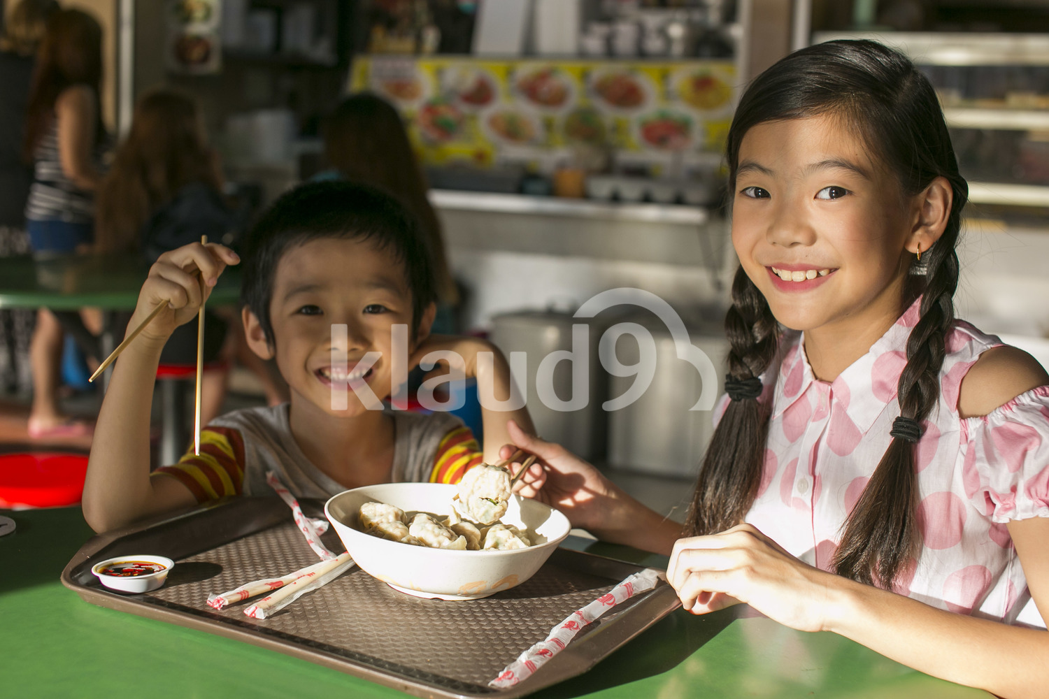 Brother and sister eating in Maxwell Hawker centre