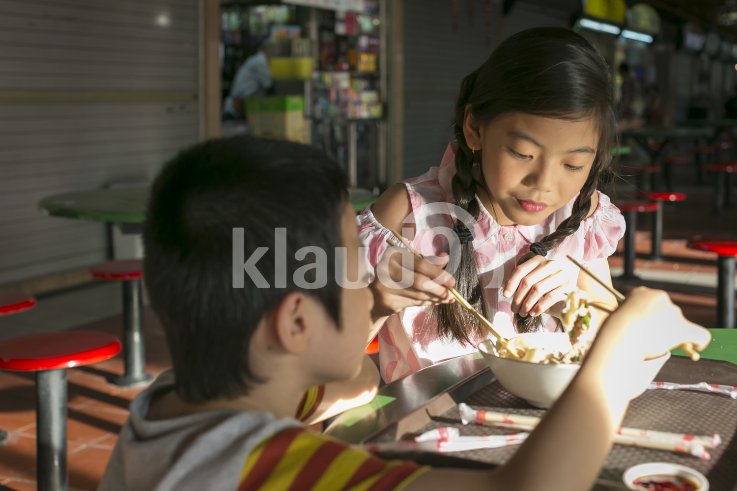 Brother and sister eating in a hawker centre