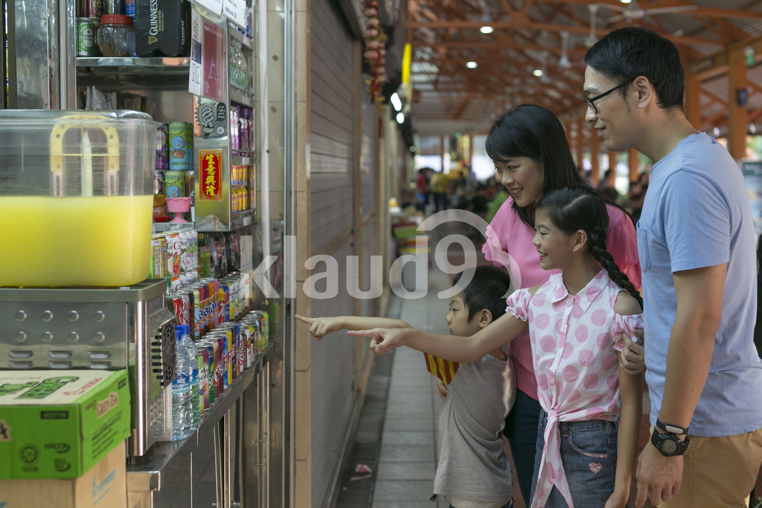 Family of four in a hawker centre getting drinks