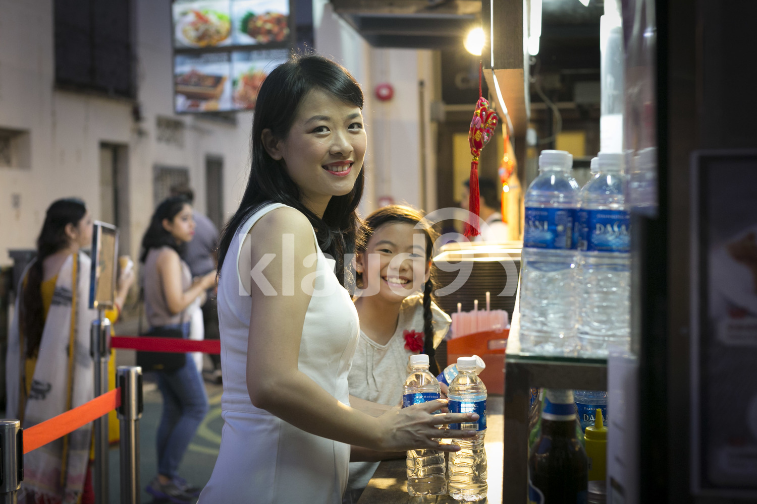 Mother and daughter buying water in a hawker