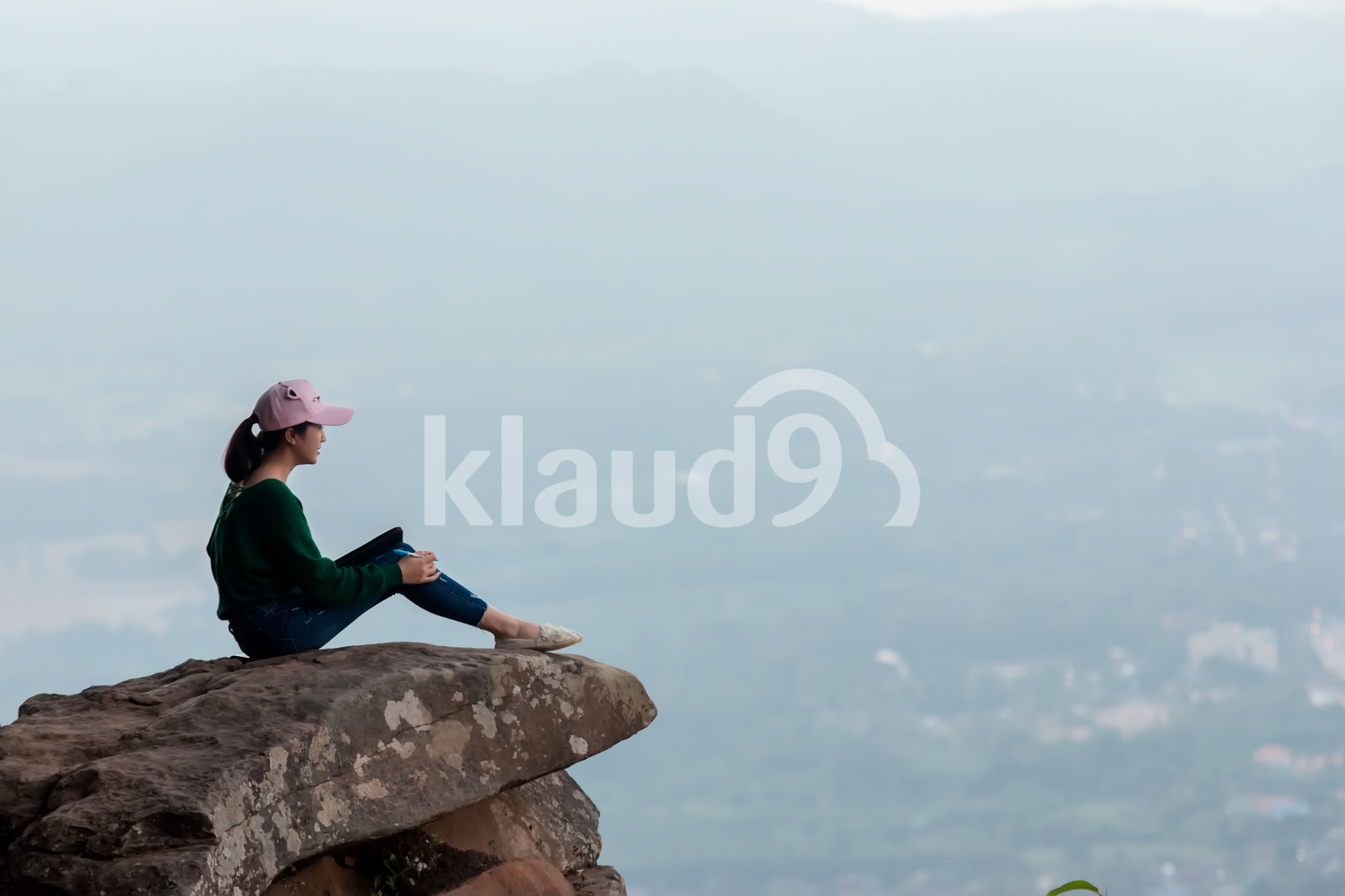 Young woman sitting on cliff's edge