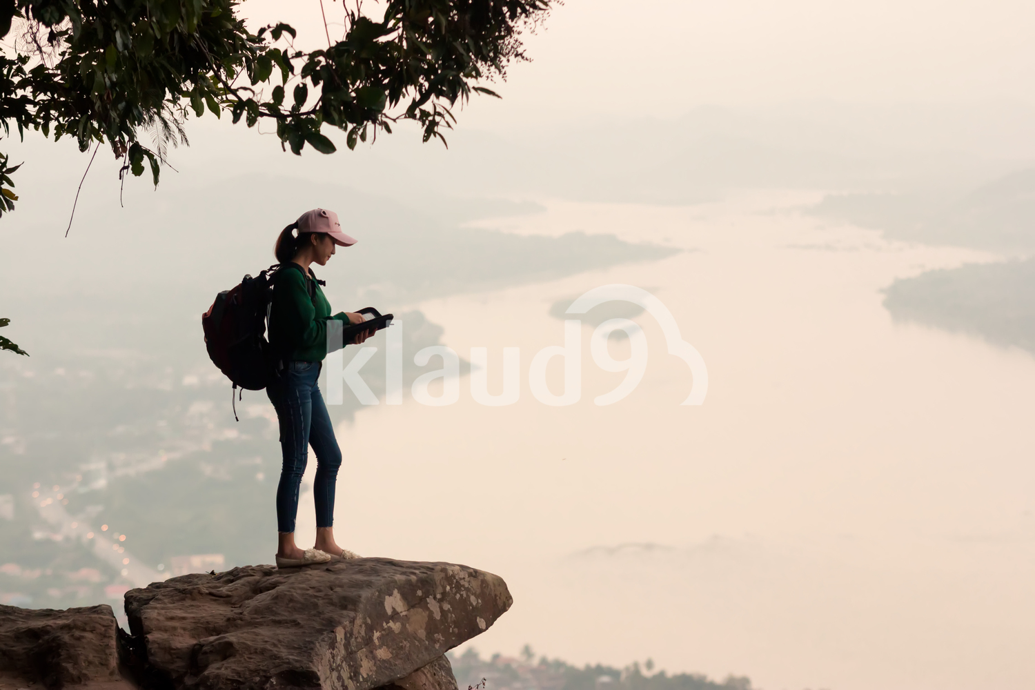 Young woman standing on cliff's edge