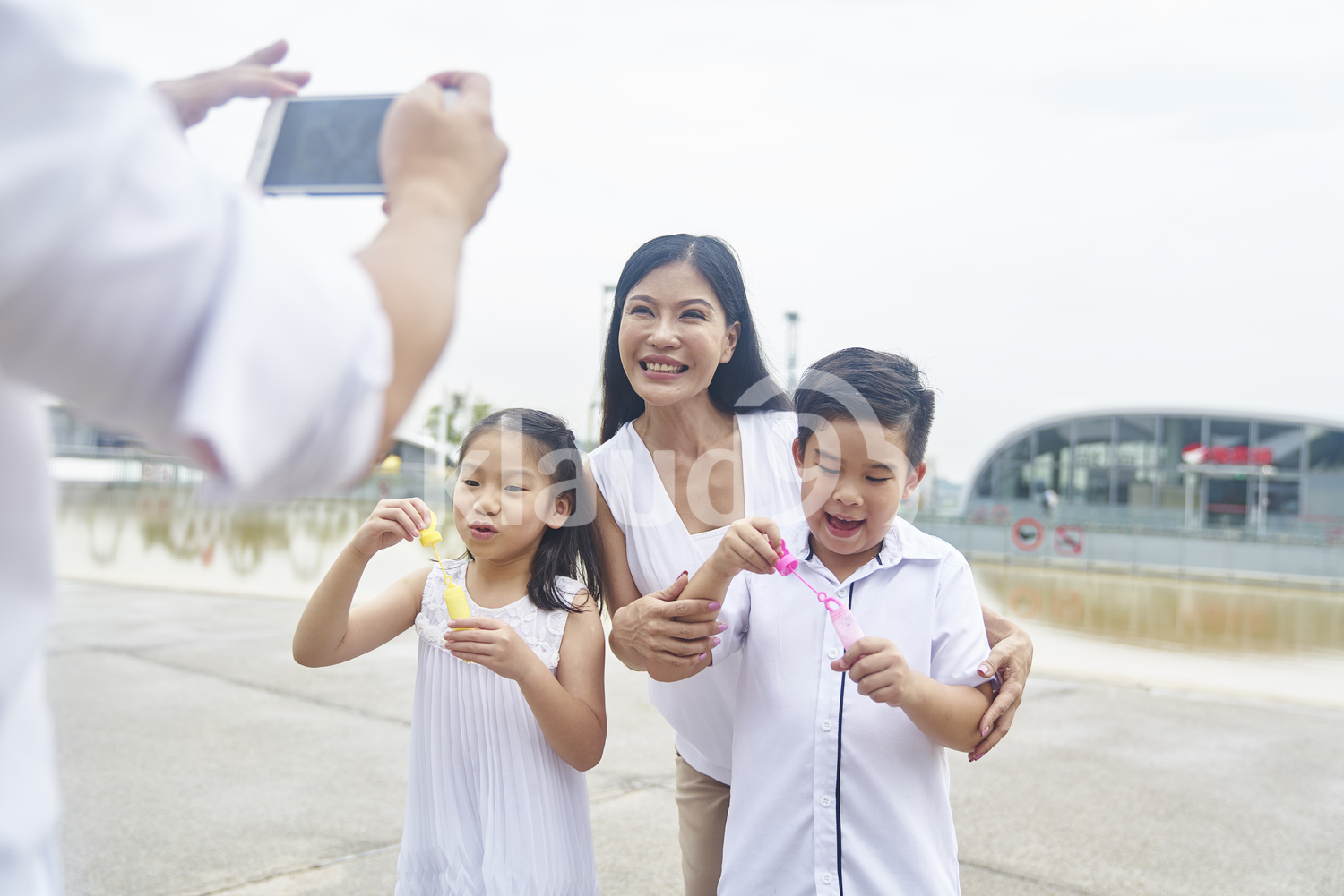 Father taking a photo of his family with bubbles