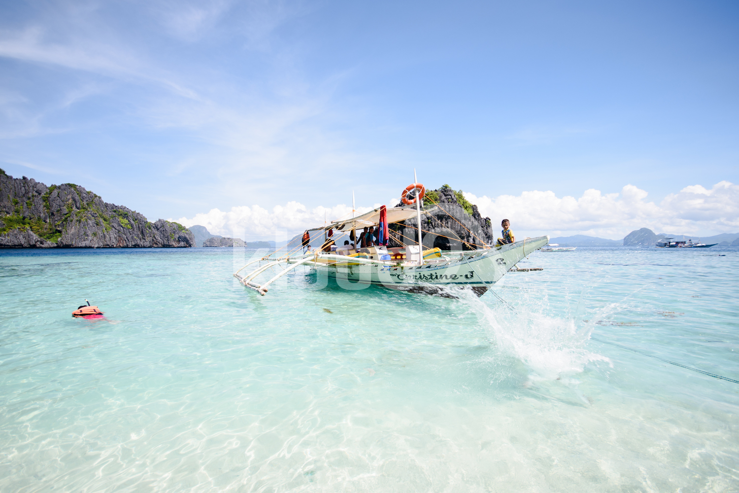 Paradise island and crystal clear water of El Nido, Palawan, Philippines with a boat in the sea