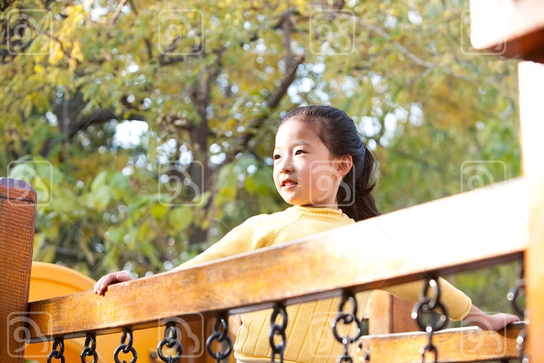 Chinese girl playing on playground toy bridge