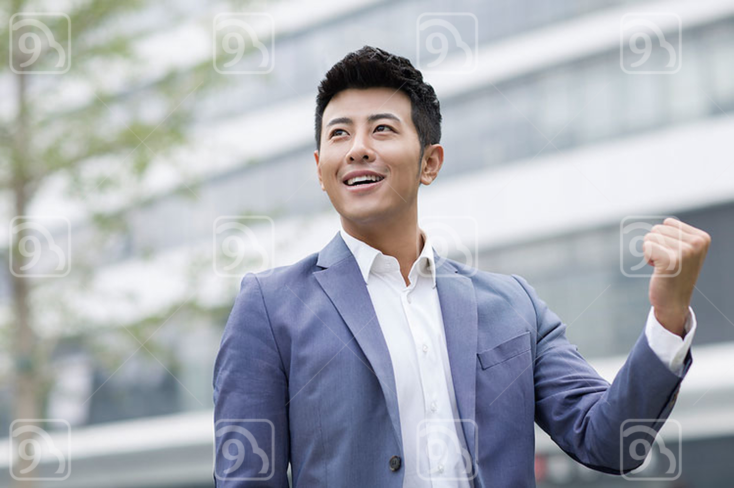 Happy Chinese businessman punching the air