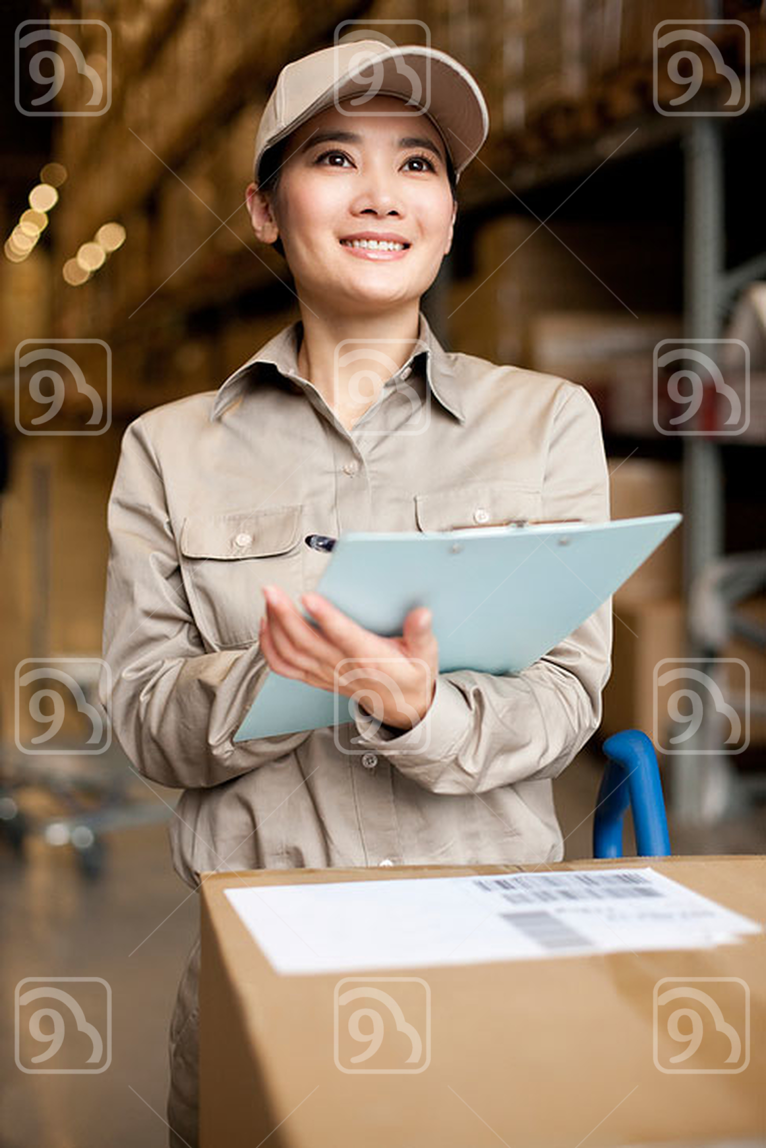 Female Chinese warehouse worker doing inventory