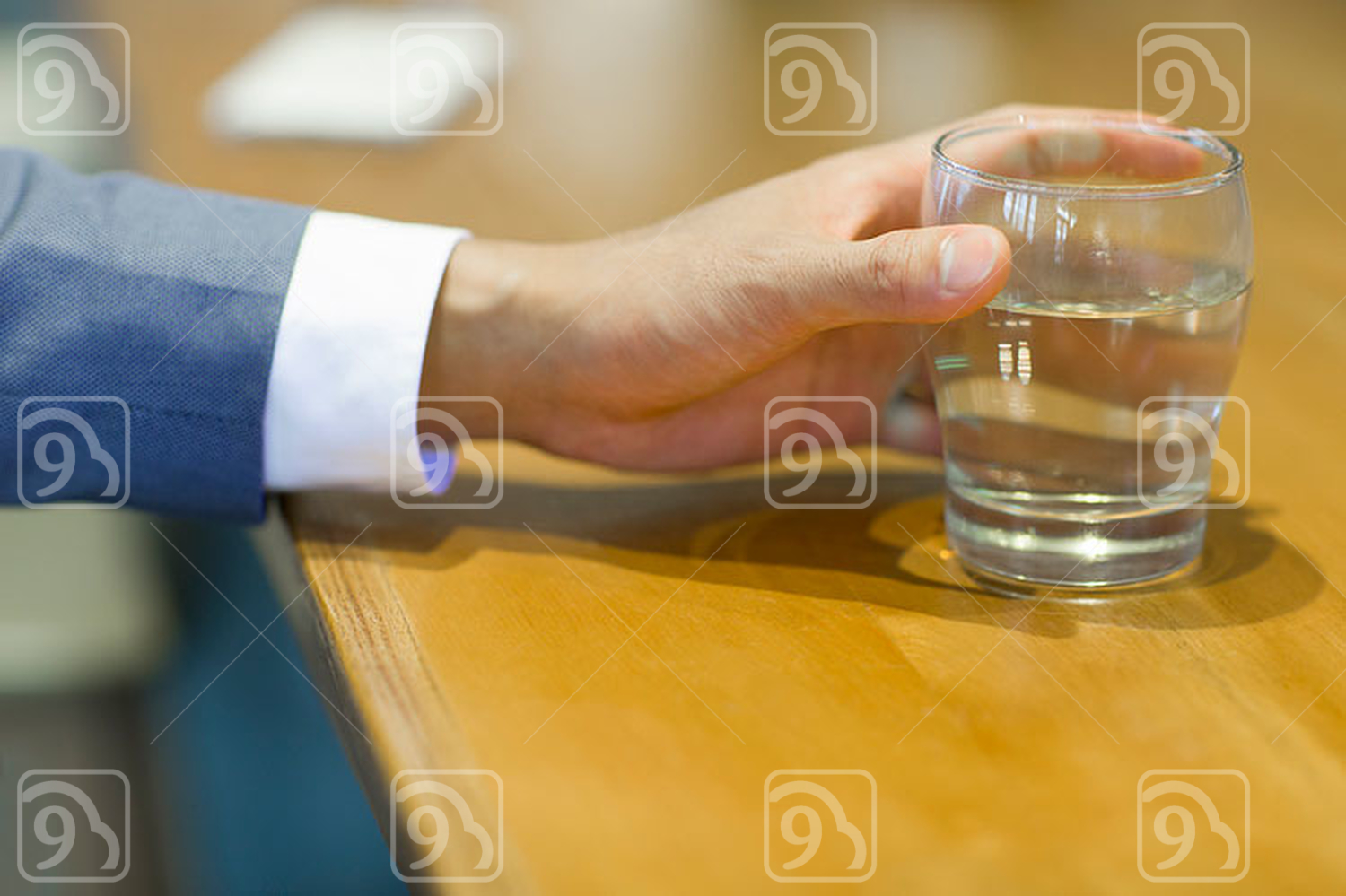 Chinese businessman holding a glass of water