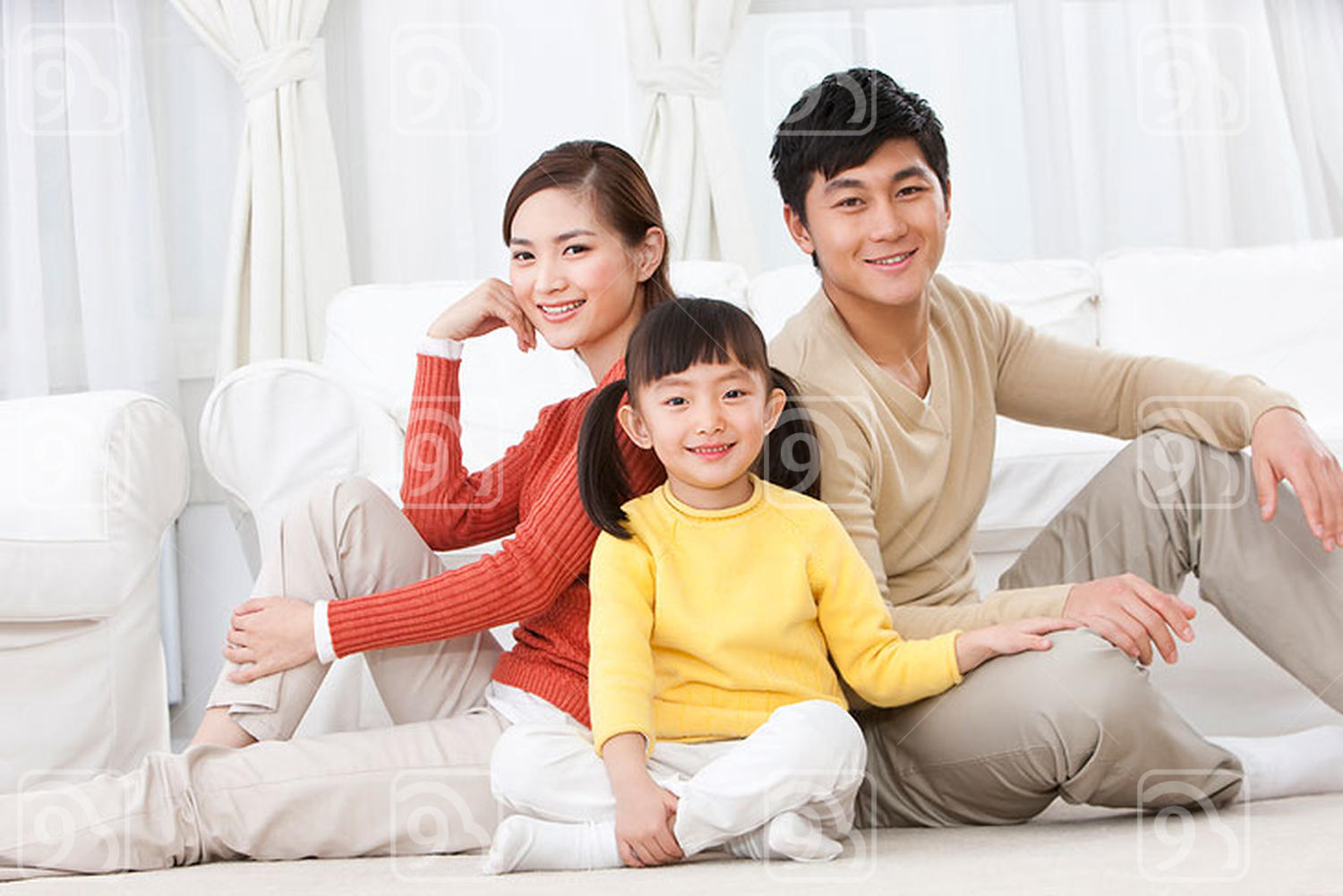 Happy young Chinese family sitting on carpet